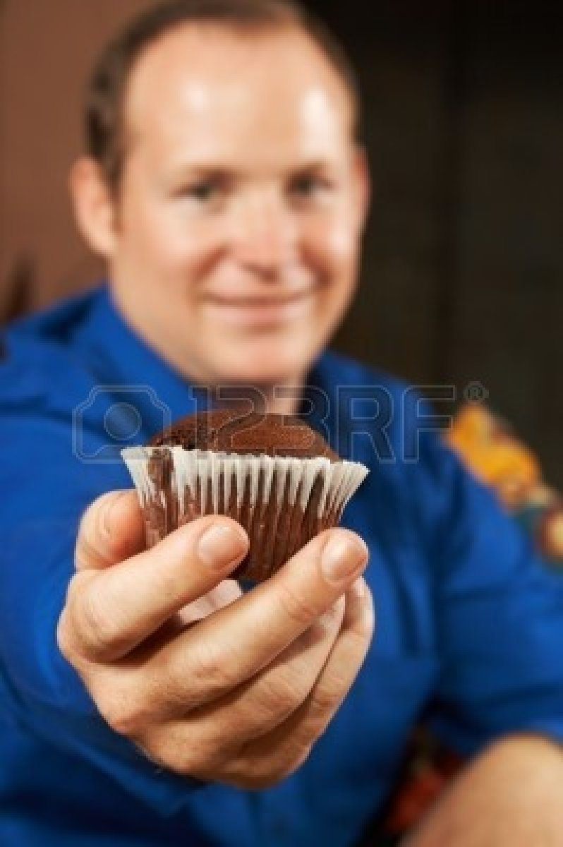 997993-sexy-young-man-in-blue-shirt-offering-you-a-chocolate-chip-muffin-shallow-depth-of-field--muffin-is-.jpg